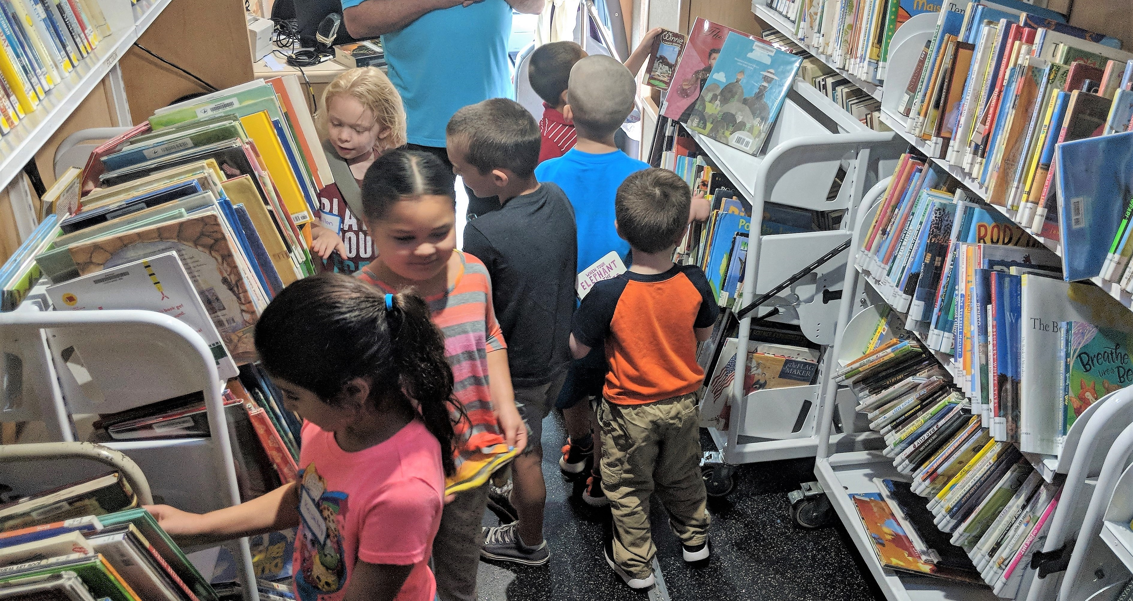 Students pick books out from the Bookmobile